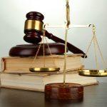 Waage vor Büchern und Richterhammer