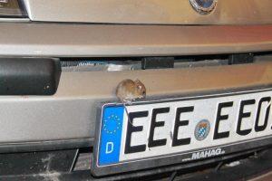 Maus sitzt auf Stoßstange bei Abgasuntersuchung