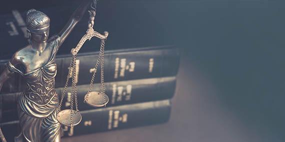 Justitia als Waage vor Büchern