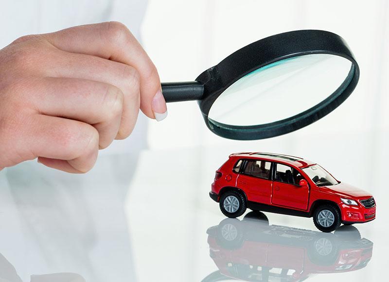 Miniatur-Auto unter einer Lupe