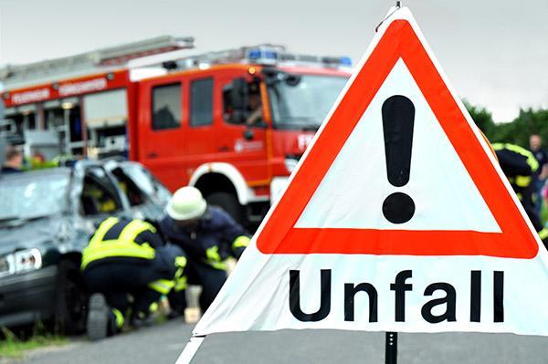 Feuerwehr an einem Unfall mit einem Warndreieck im Vordergrund
