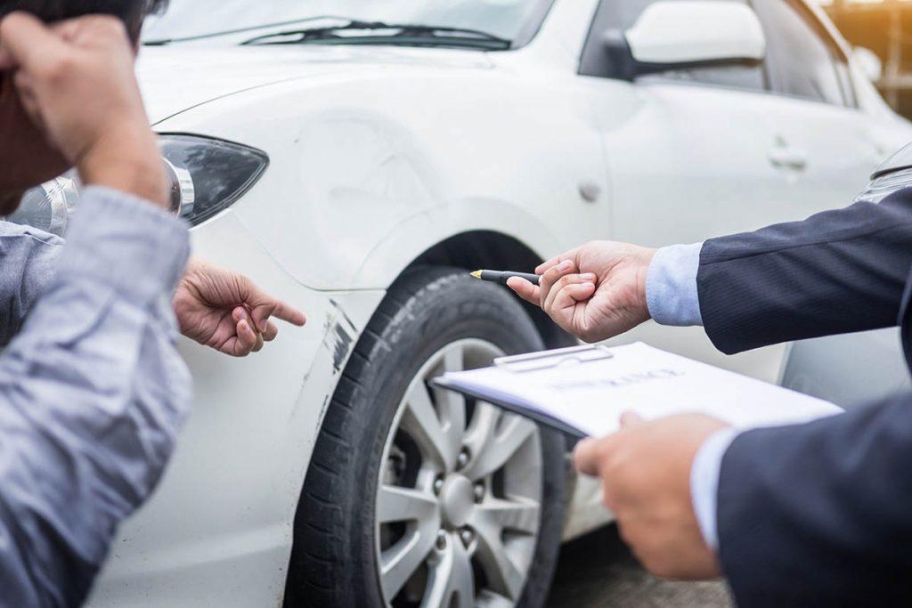 Zwei Männer prüfen Schaden an einem Auto