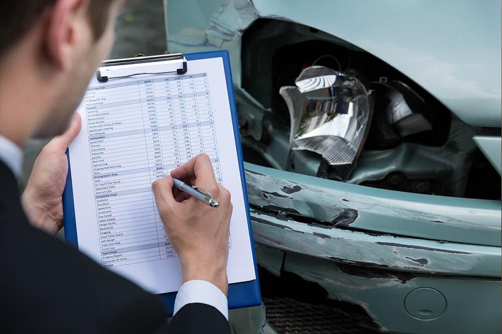Mann prüft Schaden an einem Auto