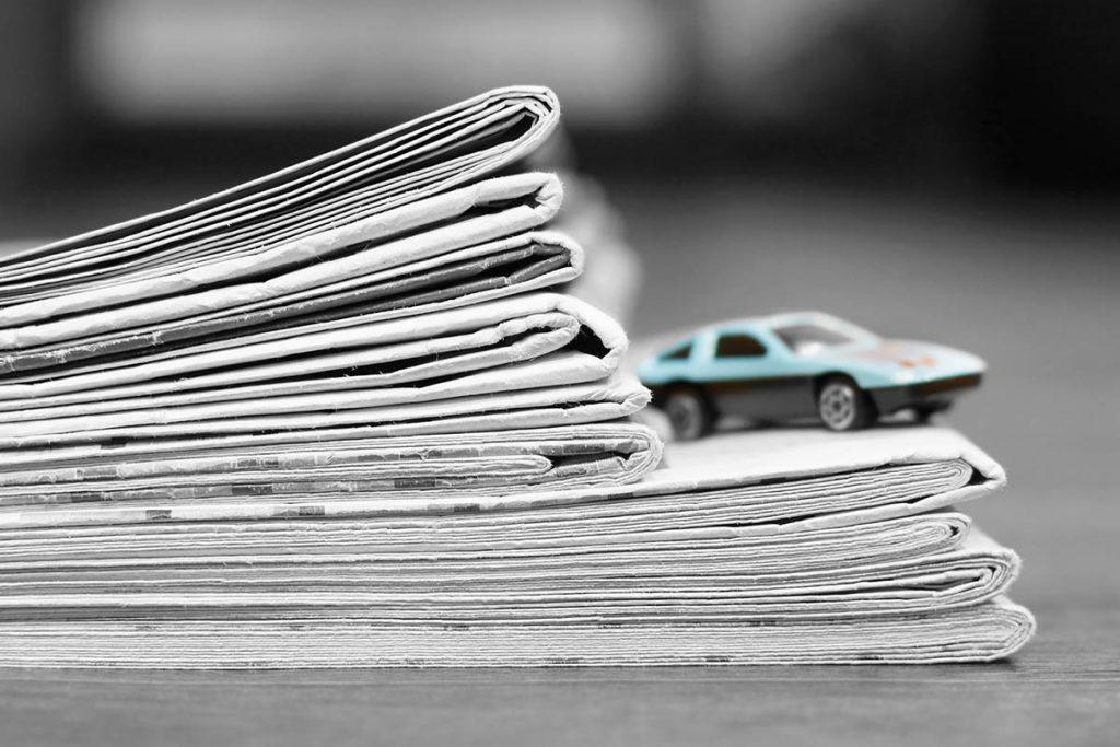 Auto steht auf Zeitungsstapel